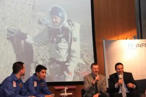 """Dirk Wagner (re) und Dr. Markus Landgraf (2. v. re) plaudern über die """"Mars-Expedition"""" der Mars Society. Das große Bild zeigt Dr. Landgraf im """"Marsanzug"""" im Norden Kanadas. Links die beiden """"Marsianer"""" Romain und Urbina."""